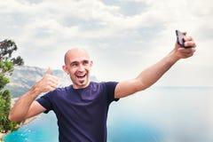 Junger Mann, der Reise selfie am Trekkingsexkursionstag nimmt - Hippie-Kerlselbstfoto am Standpunkt mit blauem Ozeanhintergrund - Lizenzfreies Stockbild