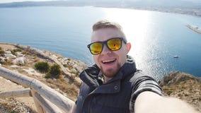 Junger Mann, der Reise selfie am Trekkingsexkursionstag nimmt Vor dem hintergrund des Meeres und der Felsen stock video footage