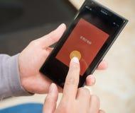 Junger Mann, der rote Tasche auf Mobile auf WeChat für chinesisches neues Jahr vorbereitet Stockbilder