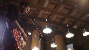 Junger Mann, der rote und weiße E-Gitarre spielt stock footage
