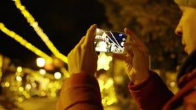 Junger Mann in der roten Jacke macht Fotos mit Smartphone am Abend auf Weihnachtsbeleuchtungshintergrund Geschossen auf ROT stock footage