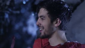 Junger Mann in der roten Kleidung lächelt und zieht langsam in Wald des verschneiten Winters um stock footage