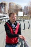 Junger Mann in der roten Weste mit Kopfhörern Stockfotografie