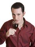 Junger Mann, der Rotwein riecht stockfotografie