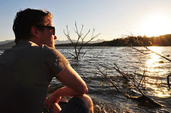 Junger Mann, der ruhig neben See sitzt Stockfotografie