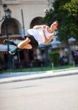 Junger Mann, der Salto in der Straße durchführt Stockfotos