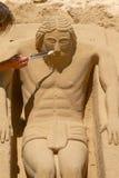Junger Mann, der an Sand-Skulptur von Jesus in Cadiz, Spanien arbeitet Stockbilder