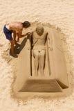 Junger Mann, der an Sand-Skulptur von Jesus in Cadiz, Spanien arbeitet Lizenzfreie Stockfotografie