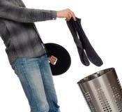 Junger Mann, der schmutzige Socken in einen Wäschekorb einsetzt Lizenzfreie Stockfotografie