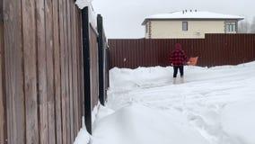 Junger Mann, der Schnee nahe dem Haus schaufelt stock footage