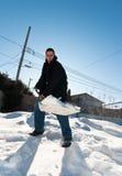 Junger Mann, der Schnee schaufelt Stockfoto