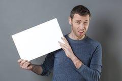 Junger Mann, der schrecklich sucht, wenn schlechten Nachrichten auf seinem Brett mit Raum nach jedem negativen Text gehalten werd Stockbild