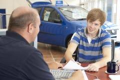 Junger Mann, der Schreibarbeit im Autoausstellungsraum ausfüllt Lizenzfreie Stockbilder