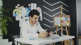 Junger Mann, der am Schreibtisch in seinem Büro sitzt und mit irgendwelchen Dokumenten und Tablet-Computer arbeitet stock video