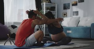 Junger Mann, der schwangere Frau während des Trainings anweist
