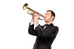 Junger Mann in der schwarzen Klage, die eine Trompete spielt Stockbild