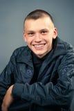 Junger Mann in der schwarzen Kleidung, lächelnd Lizenzfreie Stockbilder