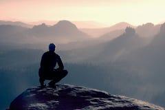 Junger Mann in der schwarzen Sportkleidung sitzt auf dem Rand der Klippe und schaut zum nebelhaften Talgebrüll Stockfotos