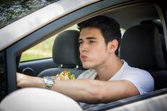 Junger Mann, der sein Auto beim Essen des Lebensmittels fährt Lizenzfreie Stockfotografie