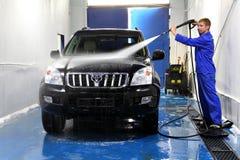 Junger Mann, der sein Auto mit Kompressionswasser wäscht Lizenzfreie Stockfotografie
