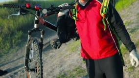 Junger Mann, der sein Fahrrad trägt stock footage