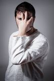 Junger Mann, der sein Gesicht mit der Hand versteckt Lizenzfreie Stockfotografie
