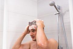 Junger Mann, der sein Haar in der Dusche wäscht Lizenzfreies Stockfoto