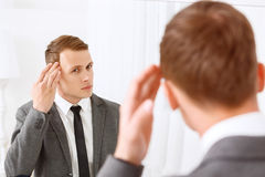 Junger Mann, der sein Haar vor Spiegel repariert Stockbild