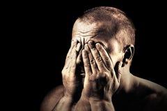 Junger Mann, der seine Augen abdeckt Stockbilder