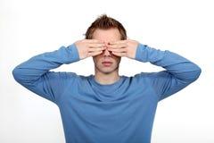 Junger Mann, der seine Augen abdeckt Lizenzfreies Stockfoto