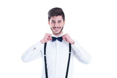 Junger Mann, der seine Fliege, lächelnd korrigiert Lokalisiert auf weißem BAC Stockfotografie
