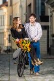 Junger Mann, der seine Freundin auf dem Fahrrad drückt lizenzfreies stockbild