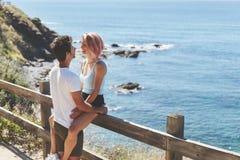 Junger Mann, der seine Freundin sitzt auf Zaun umarmt stockfotografie