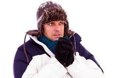 Junger Mann, der seine Hände von der Kälte löscht Stockfotografie