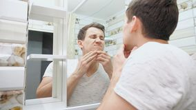 Junger Mann, der seine Haut im Badezimmer überprüft stock footage