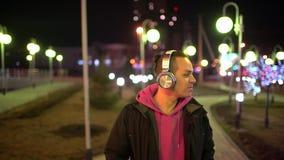 Junger Mann, der seine Kopfhörer in der Straße verwendet Porträt von tragenden Haupttelefonen des jungen Mannes beim auf die Stra stock footage