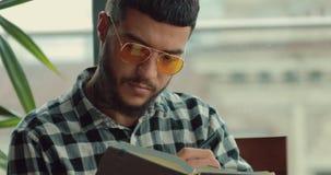 Junger Mann, der seine kreative Idee schreibt oder zukünftige Tage in Notizbuch plant stock footage