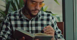 Junger Mann, der seine kreative Idee schreibt oder zukünftige Tage in Notizbuch plant stock video