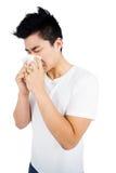 Junger Mann, der seine Nase abwischt Stockfoto