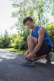 Junger Mann, der seine Sport-Spitze bindet Stockbilder
