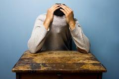 Junger Mann, der in seinem Pullover sich versteckt Stockbilder