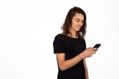 Junger Mann, der an seinem Telefon spielt Stockbild