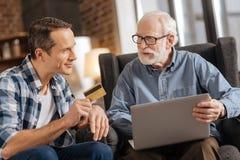 Junger Mann, der seinem Vater Bankkarte verwendet Laptop gibt Lizenzfreie Stockbilder