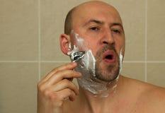 Junger Mann, der seinen Bart mit dem Rasiermesser reflektiert rasiert Stockfotos