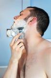 Junger Mann, der seinen Bart rasiert Stockbild