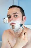 Junger Mann, der seinen Bart rasiert Stockbilder