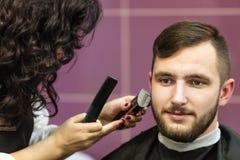 Junger Mann, der seinen Bart sich pflegen lässt Stockbild