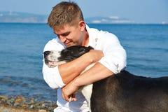 Junger Mann, der seinen Hund lächelt und umarmt Lizenzfreie Stockbilder