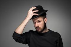 Junger Mann, der seinen Hut im Respekt anhebt und lizenzfreies stockbild