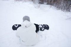 Junger Mann, der seinen Snowboard im Schnee justiert Lizenzfreies Stockbild